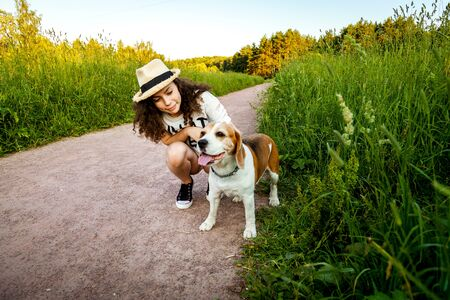 Girl with a beagle on a path in the grass.