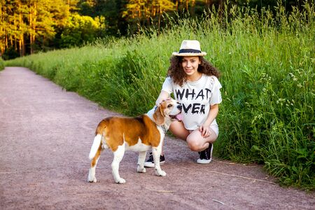 A girl with a Beagle on a path in the grass.