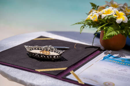 Wedding rings and wedding certificate on a tropical wedding on the background of the sea.
