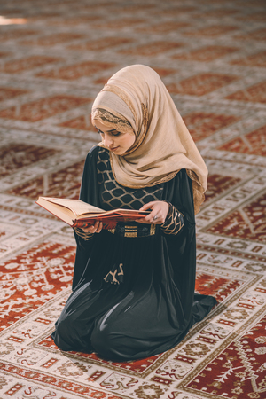 religious clothing: Young Muslim girl reading holy book Stock Photo