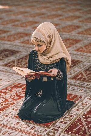 humilde: Young Muslim girl reading holy book Foto de archivo