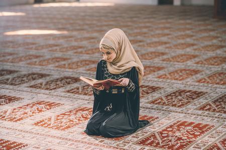 humble: Muslim woman reading holy book Koran