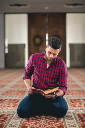 Muslim reading Koran Imagens