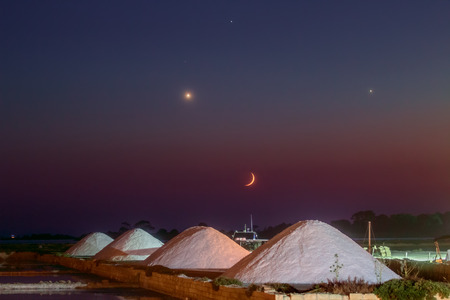 conjunction: A spectacular conjunction of Moon, Venus, Jupiter and Regolus over and old salt factory. In the foreground can be seen the salt mounds, the wind mill and the SUMPS where the sea water is evaporated to recover the crystalized salt.A soft focus filter have  Stock Photo