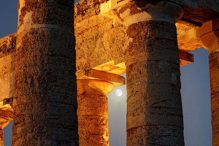 calatafimi: Blue Moon Among The Columns of Segesta Temple; Segesta is an old city in sicily founded by Elimi whose origins are not certain. The temple was built in the 5th century BC following the classic style of greek architecture.