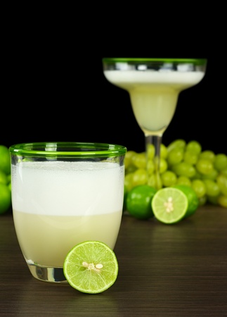 Pisco Sour, a Peruvian cocktail made of pisco, lime juice, sugar syrup and egg white with limes, grapes and another cocktail in the background (Selective Focus, Focus on the rim of the glass in front and the lime in the front) photo