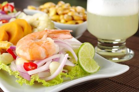 vergezeld: Peruaanse ceviche met koning vergezeld van zoete aardappelen, maïs, cancha (gebakken maïs) en de Peruaanse cocktail genaamd garnaal  Stockfoto