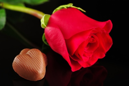 Chocolate heart with red rose photographed on black (Selective Focus, Focus on the chocolate heart) photo