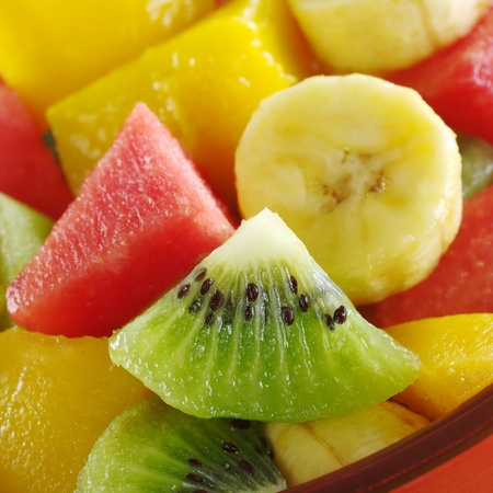 fruit salads: Fresh and healthy tropical fruit salad out of kiwi, mango, banana and watermelon pieces in an orange bowl (Selective Focus, Focus on the kiwi slice)