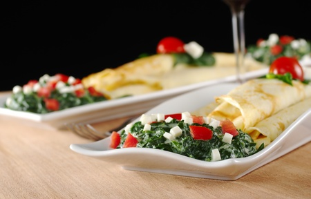 Two plates of thin, rolled crepes (pancakes) with spinach, tomatoes and cheese with a wine cup in between on wooden board with black background (Selective Focus, Focus on the front of the sauce on the first plate)  photo