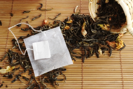 Teabag with empty white label on lose green tea with dried jasmine blossoms and a wooden tea strainer (Selective Focus, Focus on the teabag and the label) photo