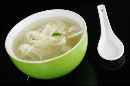 chinese noodle: Chinese noodle soup in a green bowl with a white chinese ceramic spoon photographed on black with a reflection