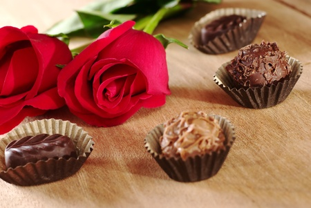 chocolate truffle: Red rose with truffles on wooden board (Selective Focus, Focus on the front of the rose and the dark chocolate truffle next to it)