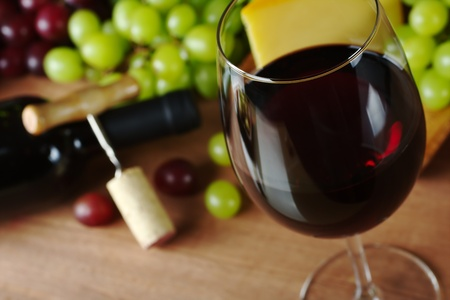 Red wine in wine glass with grapes, cheese a wine bottle and a corkscrew with cork in the background (Selective Focus, Focus on the front of the rim of the wine glass) photo