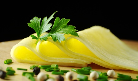 Cheese slices garnished with a parsley leaf and some shallot and pepper corns in the foreground on wooden board with black background (Selective Focus, Focus on the front of the slices and part of the parsley) photo