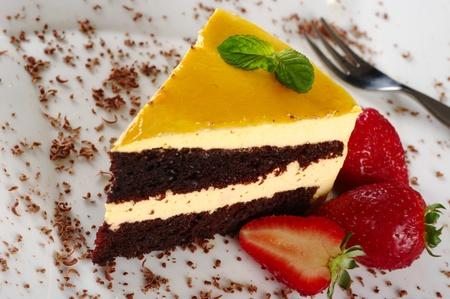 Un pedazo de pastel de lúcuma (fruto de América del Sur), decorado con hojas de menta, virutas de chocolate y fresas servido en un plato blanco con un tenedor de pastelería (enfoque selectivo, foco de la hoja de menta)