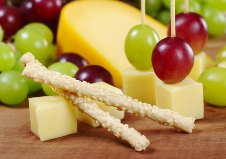 Sesame sticks with cheese and red and white grapes on wooden board (Selective Focus, Focus on the upper sesame stick) photo