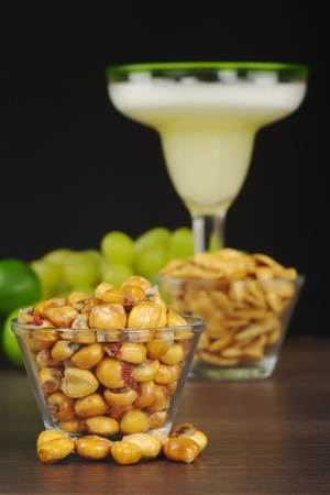 Canchas: Peruvian roasted corn eaten as snack with the cocktail called Pisco Sour in the back with limes and grapes (Selective Focus, Focus on the front)  photo