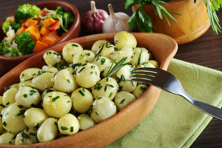 Small potatoes with herbs, such as parsley, thyme and rosemary with a fork; with fried vegetables, garlic and fresh herbs in a wooden mortar in the background (Selective Focus, Focus on the rosemary branch on the potatoes and the fork and potatoes around  photo