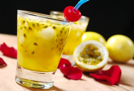 Passion-fruit juice with a drinking straw and a maraschino cherry as well as passion-fruit and rose petals in the background on wooden board (Selective Focus, Focus on the maraschino cherry)
