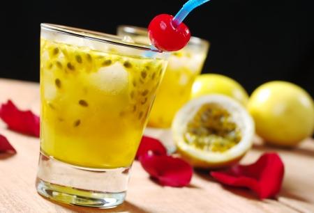 sappen: Passie-vruchtensap met een drinken stro, evenals een maraschino cherry en passievrucht en rose bloemblaadjes in de achtergrond op een houten bord (selectieve aandacht, Focus op de maraschino cherry) Stockfoto