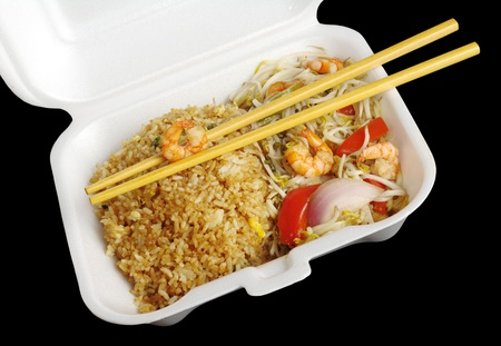 Chinese takeout food: Fried rice with king prawns and vegetables with wooden chopsticks in a   box photographed from top on black  photo