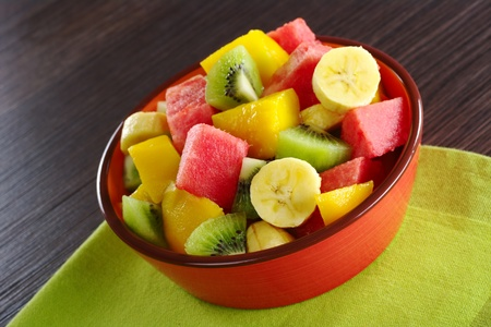 Fresh fruit salad made of banana, kiwi, watermelon and mango pieces in orange bowl (Selective Focus, Focus on the front of the bowl and the fruits in the front) Stock Photo - 8692225