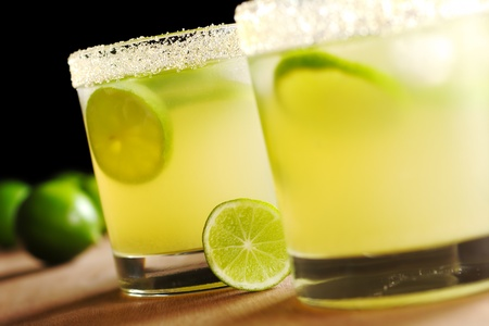 Fresh lemonade with lime slices and ice cubes in a sugar rimmed glass on wood with limes in the back on black background (Very Shallow Depth of Field, Focus on the glass in the back and the lime slice standing before it) Stock Photo - 8692207