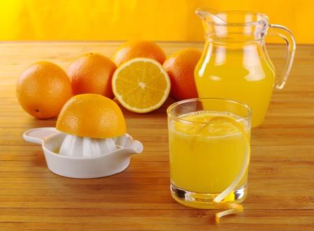 Fresh orange juice with orange juice squeezer, oranges and a jar of orange juice on wooden mat with orange background (Selective Focus)