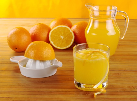 tomando jugo: Zumo de naranja con squeezer de jugo de naranja, naranjas y un frasco de jugo de naranja en madera tatami con fondo anaranjado (enfoque selectivo)