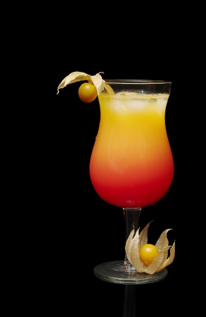 tequila: The Cocktail Tequila Sunrise with Physalis Fruit as Decoration isolated on Black Background Stock Photo