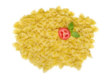 Pasta named Farfalle unprepared decorated with basil leaves and tomato slice photo