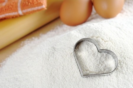 Heart shaped cookie cutter on flour with eggs, rolling pin and dishcloth in the background (Selective Focus, Focus on the cookie cutter) Stock Photo