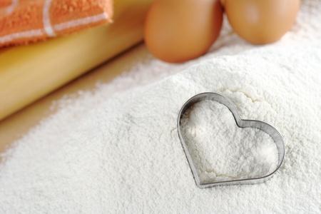 harina: Herramienta de corte de cookie en harina con huevos, rodillo y pa�o de cocina en segundo plano (enfoque selectivo, centrarse en la herramienta de corte de cookie) en forma de coraz�n Foto de archivo