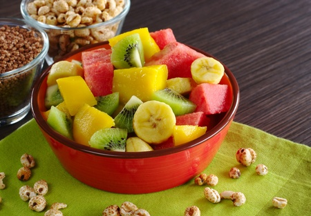 puffed: Fresh fruit salad made of banana, kiwi, watermelon and mango pieces in orange bowl with cereals (puffed wheat and puffed chocolate quinoa) (Selective Focus, Focus on the front of the bowl and the fruits in the front)