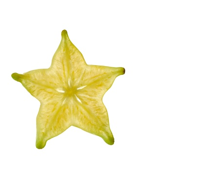 A yellow carambola slice photographed from close using light friom the back to highlight the details. photo