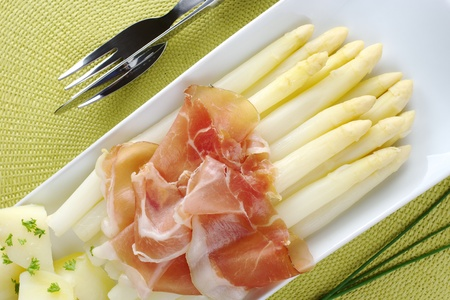 Fresh cooked white asparagus served with serrano ham and potatoes on long plate with chives and cutlery on the sides photo