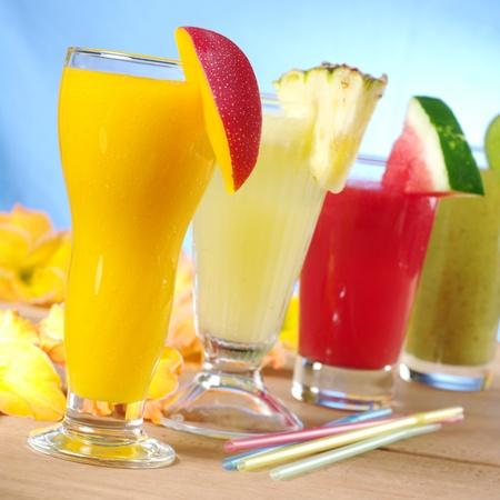 juice fruit: Mango, ananas, anguria e kiwi frullato con cannucce su legno (Focus selettiva, Focus sul frullato di mango nella parte anteriore)