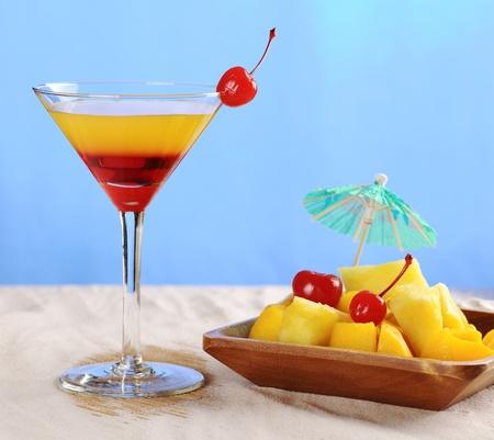 Cocktail à la cerise sur le rebord du verre et tropical fruits (ananas, mangue) dans un bol en bois, photographié sur sable blanc avec fond bleu (sélective Focus, Focus sur la cerise sur le verre, les parties de la jante de verre et les fruits de couleur jaune-rouge Banque d'images - 8852351