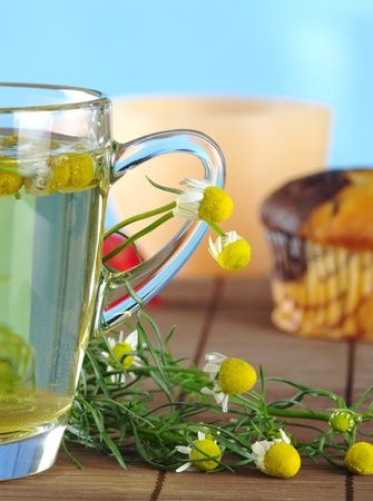 Fresh chamomile tea and flowers with muffin and candle in the background (Selective Focus, Focus on chamomile flowers and handle of cup) Stock Photo - 8852336