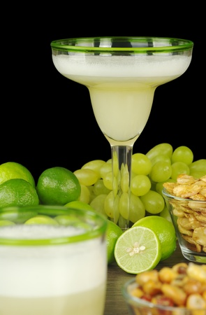 Pisco Sour, a Peruvian cocktail made of pisco, lime juice, sugar syrup and egg white. The cocktail is surrounded by grapes, limes, and Peruvian snacks, habas and canchas. (Selective Focus, Focus on the glass in the back) photo