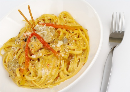 pretzel stick: Fettuccine with chicken, mushrooms and red pepper garnished with salt sticks with a fork on white (Selective Focus)  Stock Photo