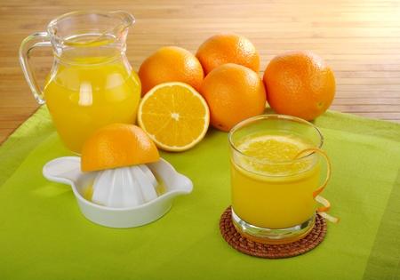 juice squeezer: Fresh orange juice with orange juice squeezer and oranges on green and a wooden mat (Selective Focus)