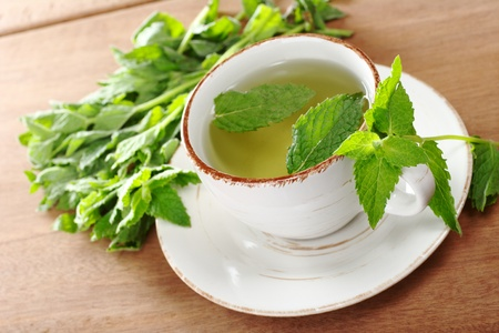 Tea made of fresh mint leaves on wood (Selective Focus, Focus on the front of the cup and the top of the mint leaves on the handle)  Stock Photo - 8934342