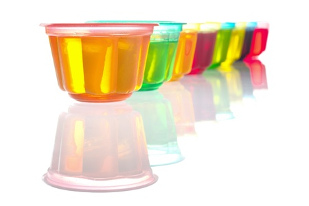 Colorful jellies in plastic bowls arranged in a row on white (Selective Focus, Focus on the first jelly)  photo