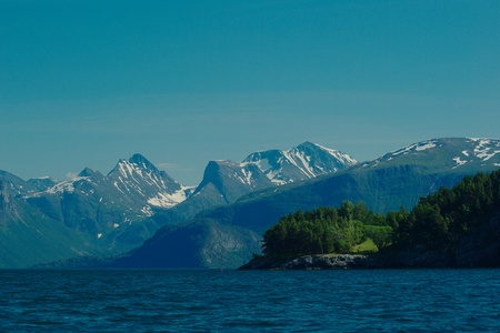 The Romsdalsfjorden close to Andalsnes in Norway in summer with green trees and snow on the top of the mountains photo