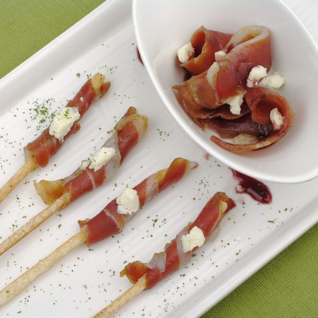 garnish: Thin bacon slices wrapped around thin salt sticks and served on a white rectangular plate on a green place mat
