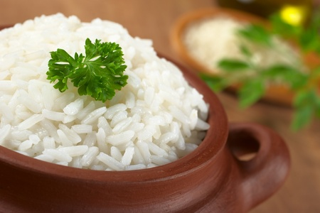 rice crop: Cooked white rice garnished with parsley in a rustic bowl (Selective Focus, Focus on the parsley and the rice around)