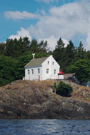 White light house on cliff in a Norwegian fjord Stock Photo - 9364859