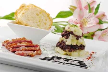 Starter with Duck Meat, Apples, Blood Sausage and Baguette, on white plate with Flower in Background (Selective Focus,Tilted) Stock Photo - 9088219